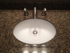 Widespread brushed nickel faucet with a white under mount sink.